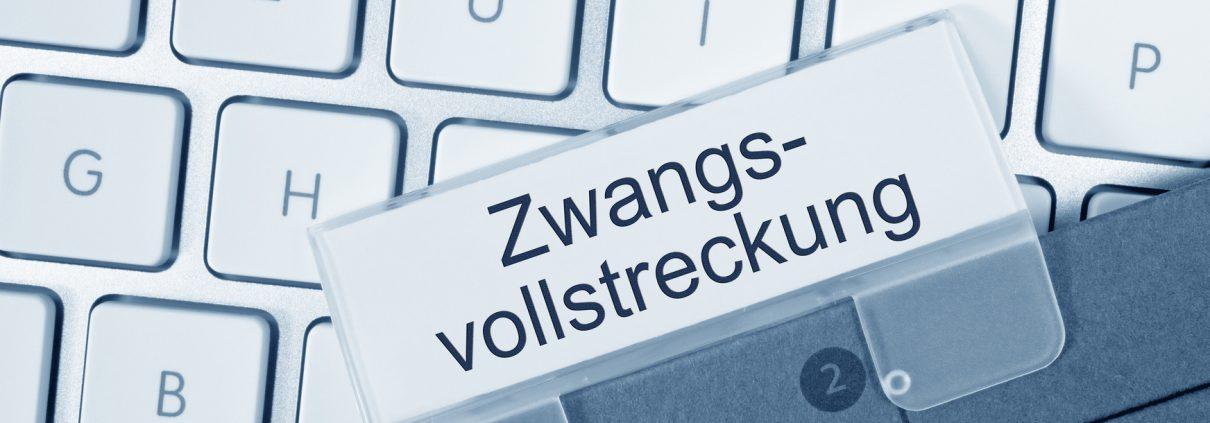 Computertastatur, auf der eine Akte mit dem Wort Zwangsvollstreckung liegt